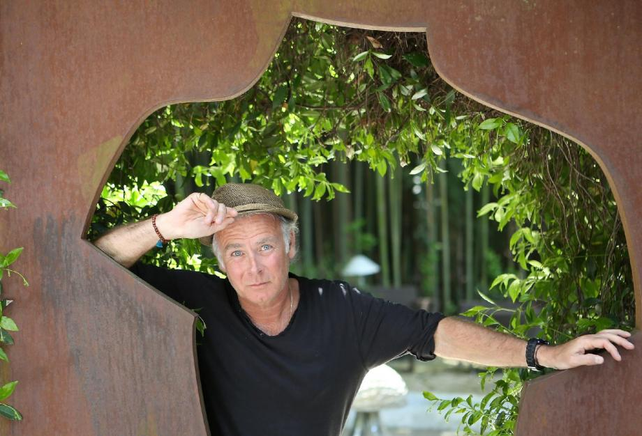 Franck Dubosc prend la pause, appuyé sur une sculpture de Sosno, dans le jardin du Moulin de Mougins.