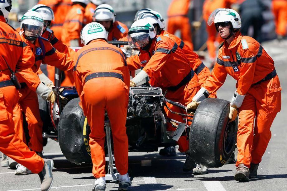 Le personnel de sécurité évacue la Marussia accidentée de l'Anglais Max Chilton.