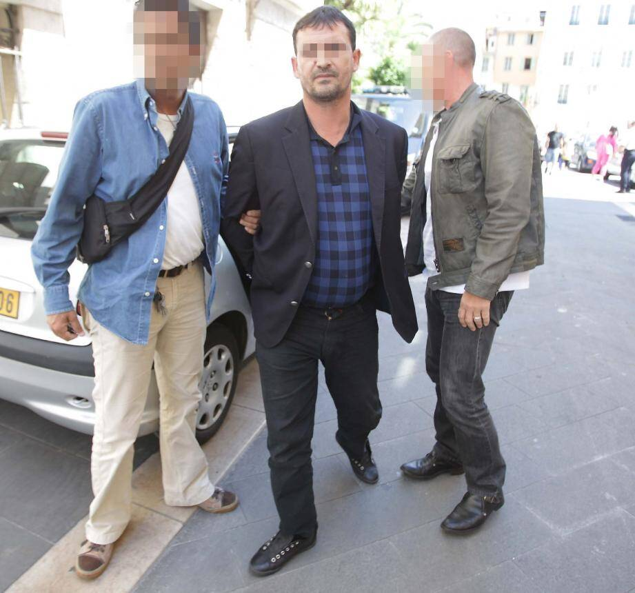 Goran Hamdivoc, le chef de réseau présumé, encadré par les policiers à son arrivée au palais de justice, hier.