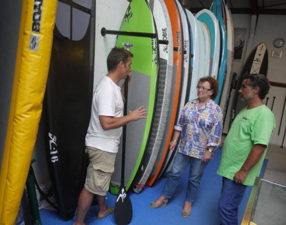 Les frères Wuilmart, dans leur showroom, expliquent à Maryse Dujarric les progrès de la technique appliquée au matériel de stand-up paddle.