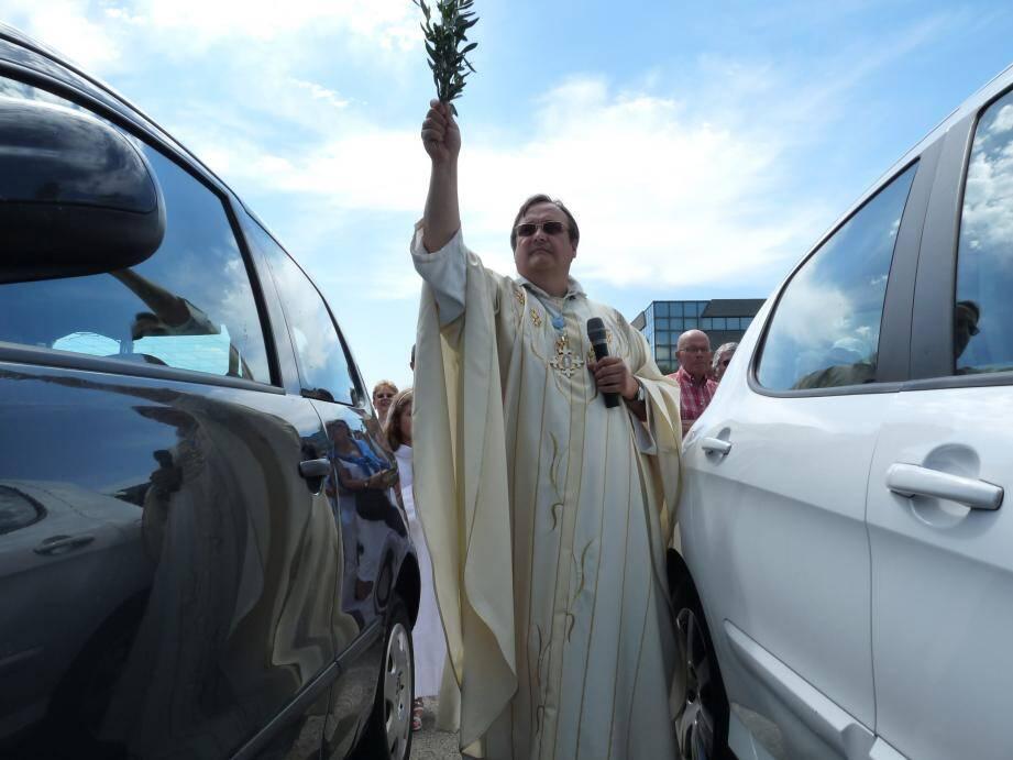 Le père Astre en train de bénir les véhicules lors de la Saint-Christophe