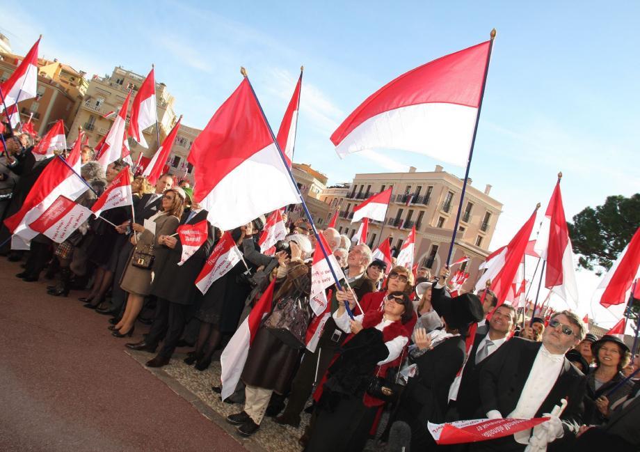 Chaque année, les Monégasques accrochent les drapeaux aux fenêtres et en amènent d'autres sur la place du palais. Une ambiance en rouge et blanc pour honorer le souverain.