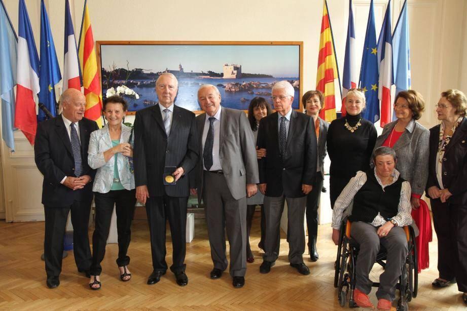 Dans le bureau du maire, Jean Poulit, médaille à la main, entouré de son épouse, du maire ainsi que de nombreux élus du conseil municipal.