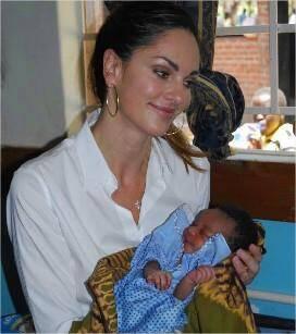 Tasha de Vasconcelos portant dans les bras un enfant né dans des conditions saines, dans un hôpital construit sous l'impulsion de sa fondation, AMOR, au Malawi.