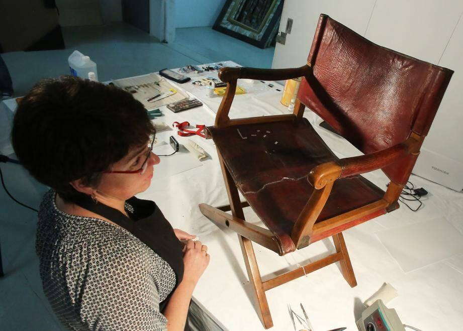 Céline Bonnot-Diconne au chevet du fauteuil en cuir pliant de l'Empereur datant de 1808