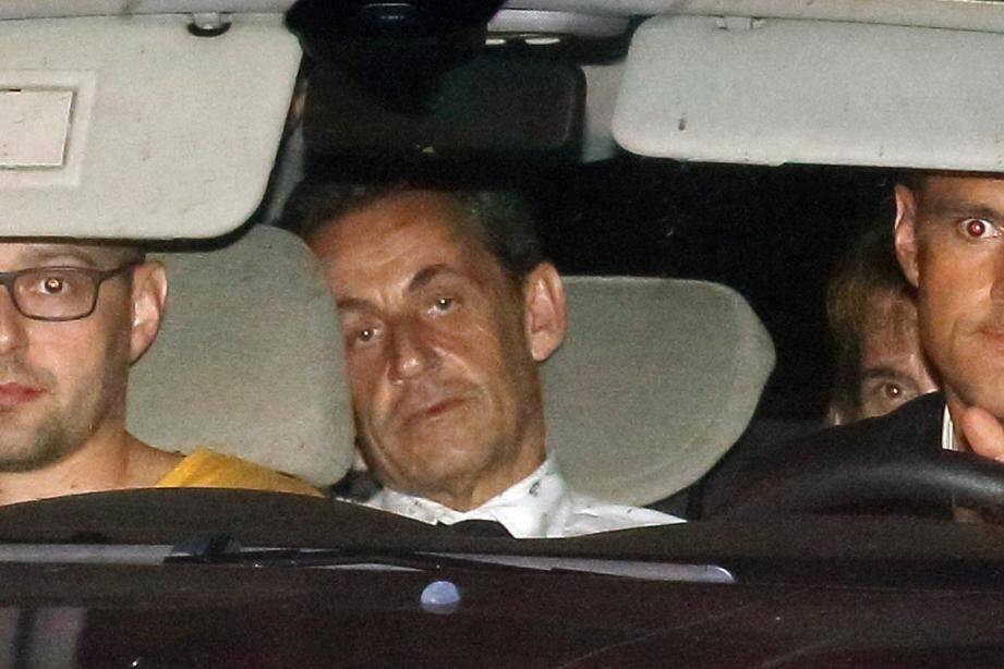 L'ancien président Nicolas Sarkozy emmené par les policiers de la brigade financière devant un juge à Paris tard mardi soir.