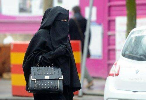 Une femme vêtue d'une forme de voile islamique intégral, le niqab, dans une rue de Roubaix dans le nord de la France, le 9 janvier 2014.