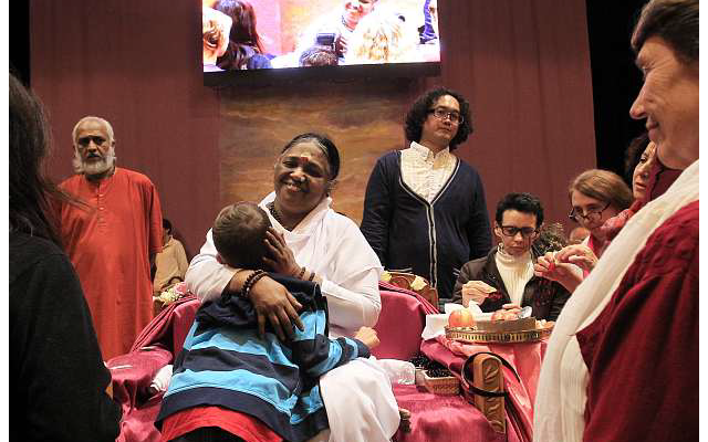 Mata Amritanandamayi prend la tête de ses « fidèles » sur son épaule droite, les entoure de ses bras pendant une dizaine de secondesen moyenne avant de leur offrir un baiser ou des pétales de fleurs ou un bonbon.