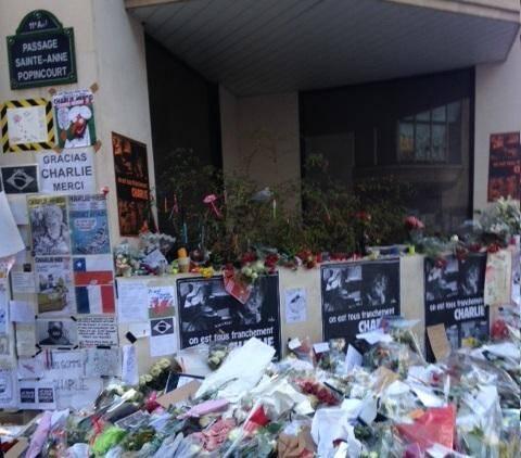 Au siège de Charlie Hebdo, fleurs, dessins et bougies devant les portraits des dessinateurs tués