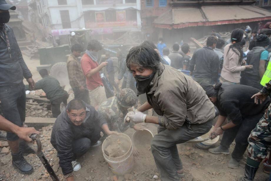 Toute la journée hier, à Katmandou, la population et les secours se sont activés pour tenter de retrouver des survivants sous les décombres. (AFP)