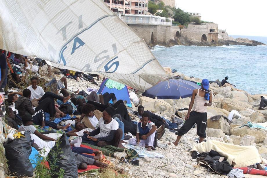 Sur les rochers, à la frontière franco-italienne de Menton, une grande voile de bateau sert désormais de parasol ou parapluie aux migrants toujours stationnés sur les rochers, côté italien.