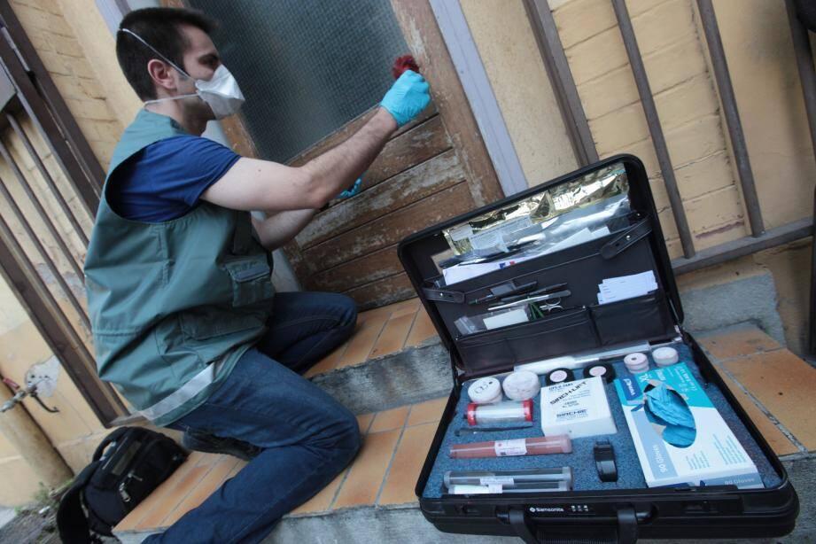 Un technicien de la police scientifique et technique effectue une recherche de traces.