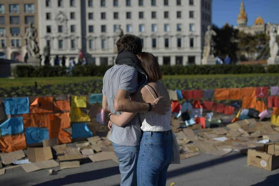 Un couple se tenant devant le Catalunya square à Barcelone, aux lendemains des attaques meurtrières de Paris.