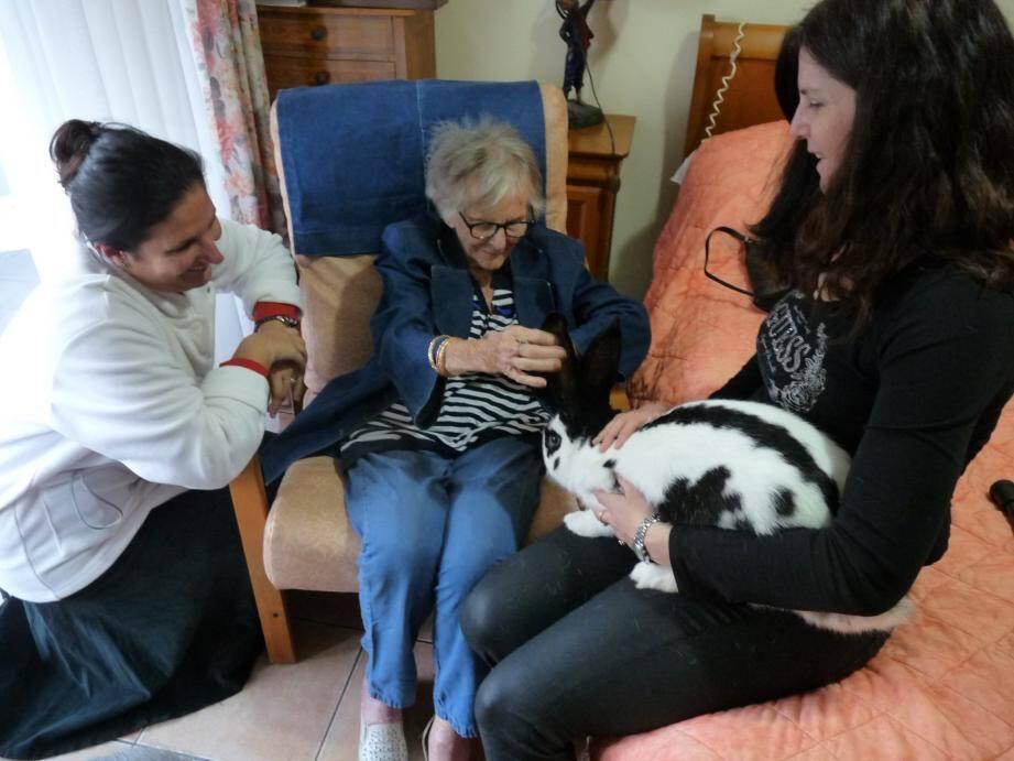 Yvette, avec Laura et Nathalie, caresse les grandes oreilles de Snoopy, un lapin géant. Grâce à lui, elle oublie ses tracas du quotidien.