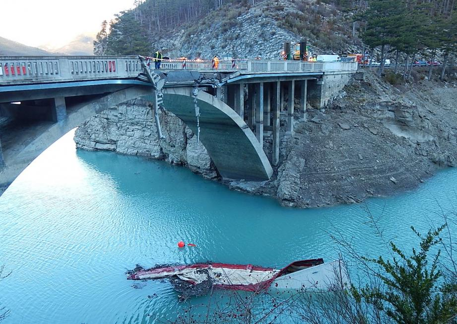 Le semi-remorque couché sur le flanc dans les eaux glacées du lac de Saint-André-les-Alpes, le long de la RN 202.