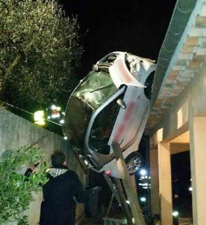 Une Smart a chuté en contrebas de la route, se retrouvant en équilibre précaire entre le toit d'une villa et le mur d'une copropriété.(DR)