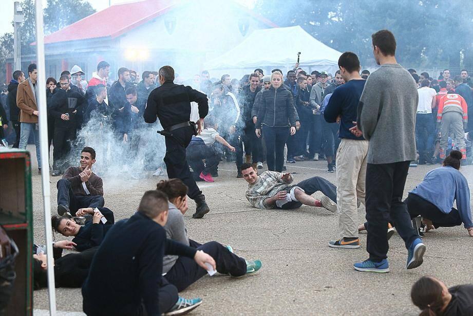La « bombe » qui vient d'exploser devant un stand de pizza, dégageant un panache de fumée, laisse plusieurs spectateurs à terre.