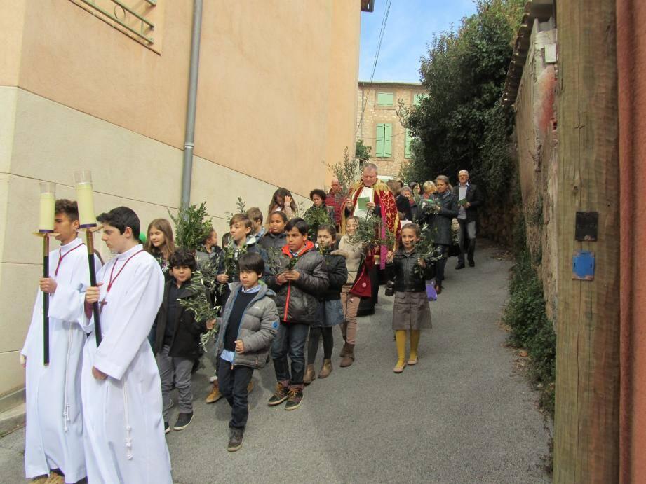Après la bénédiction des Rameaux, la procession, enfants en tête suivis des fidèles, s'est étirée jusqu'à l'église paroissiale.