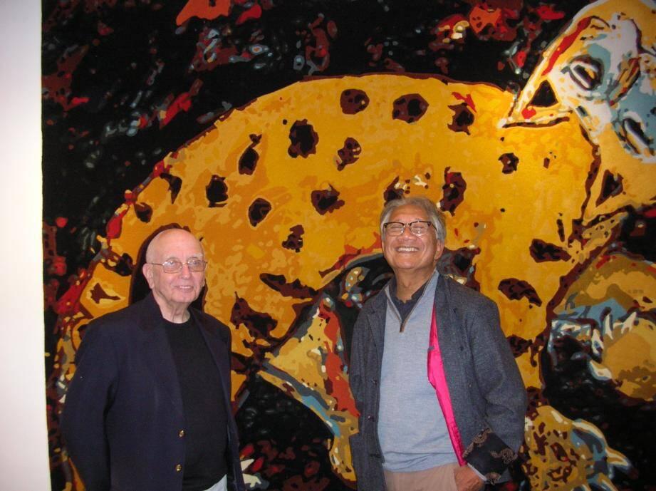 Roger Gal (à gauche) et Lek Nakarat devant une œuvre de Jacky Coville reproduite sous forme de tapisserie.
