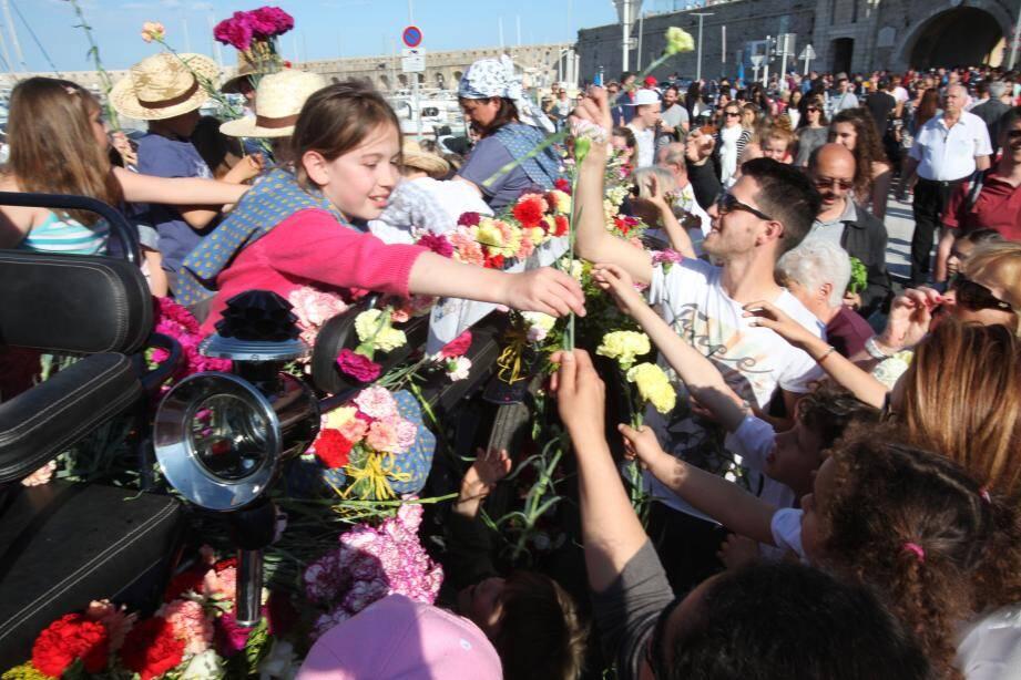 « Une fleur, une fleur ! ». Sur le port, la foule a pris d'assaut les chars. Des danseuses vêtues de pétales ont apporté une touche de poésie à cette bataille de fleurs.