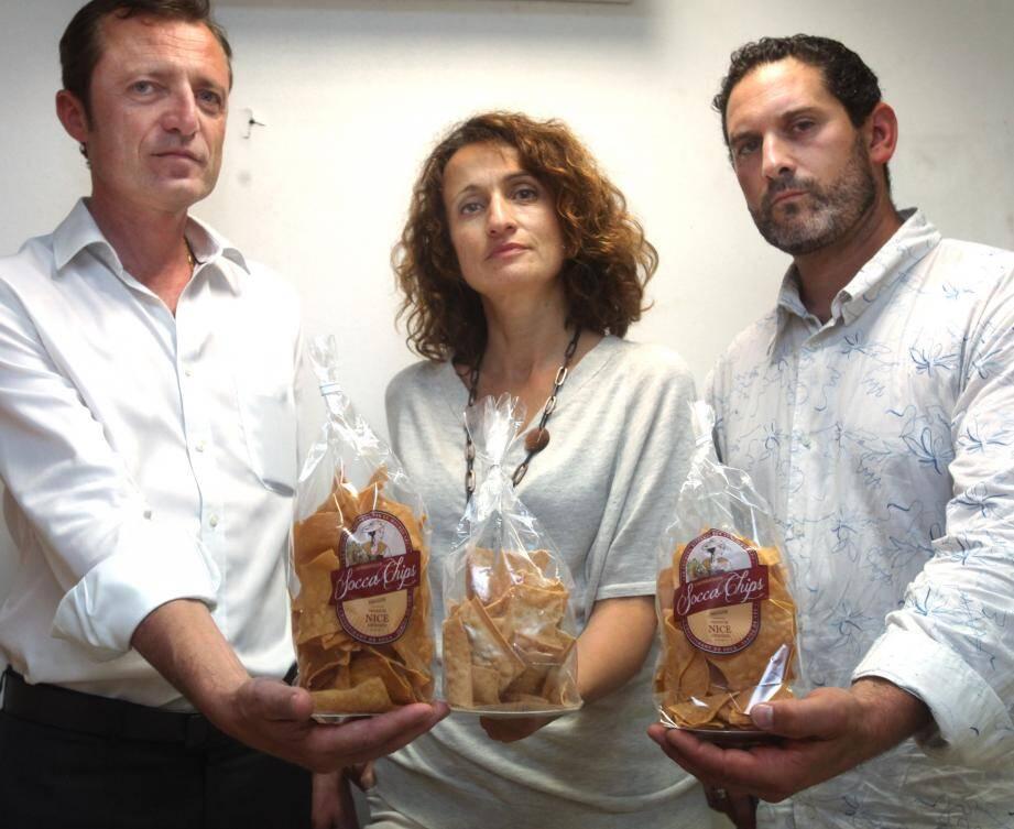 Me Jérôme Zuccarelli, et Luc Salcedo présentent les paquets de Socca Chips. Fabienne Rigourd, elle, montre celui du « concurrent déloyal ».