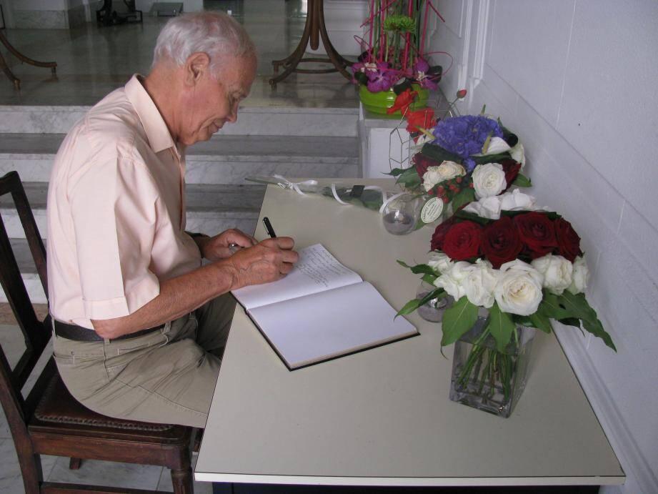 Une petite table, un bouquet bleu-blanc-rouge, un bouquet rouge et blanc, et un registre de condoléances rempli de pensées émues et horrifiées.