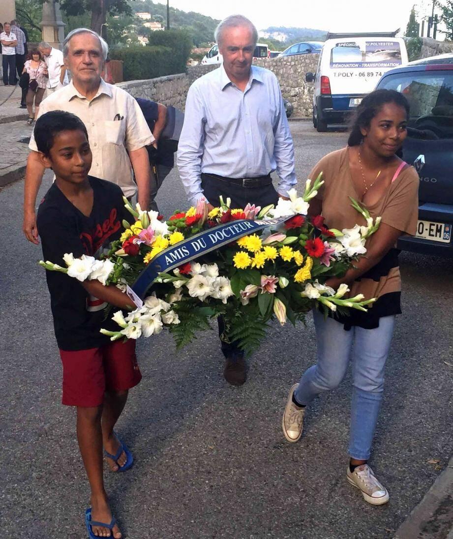 Une gerbe a été déposée par le maire et le président de l'association, ici accompagnés par deux adolescents.