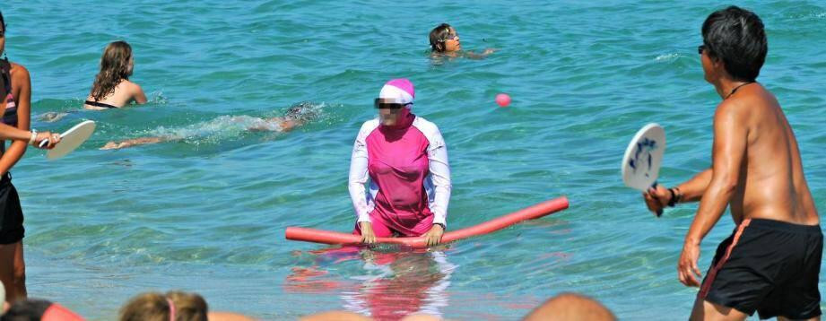 Une femme portant un burkini à la plage.