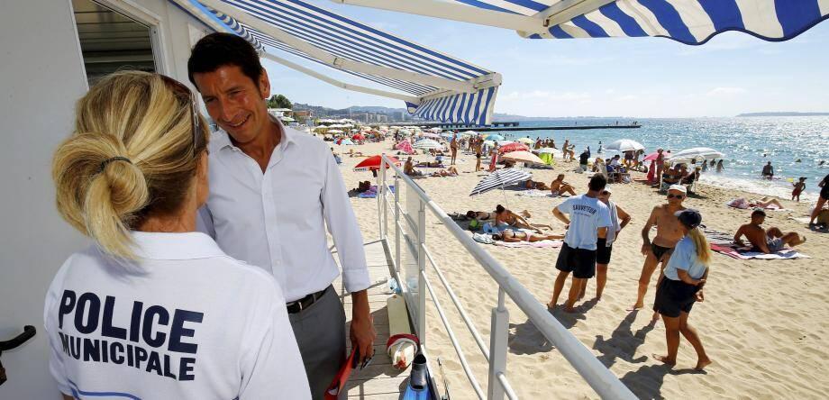 Davis Lisnard, maire de Cannes, sur une plage de sa commune en compagnie d'une policière municipale.