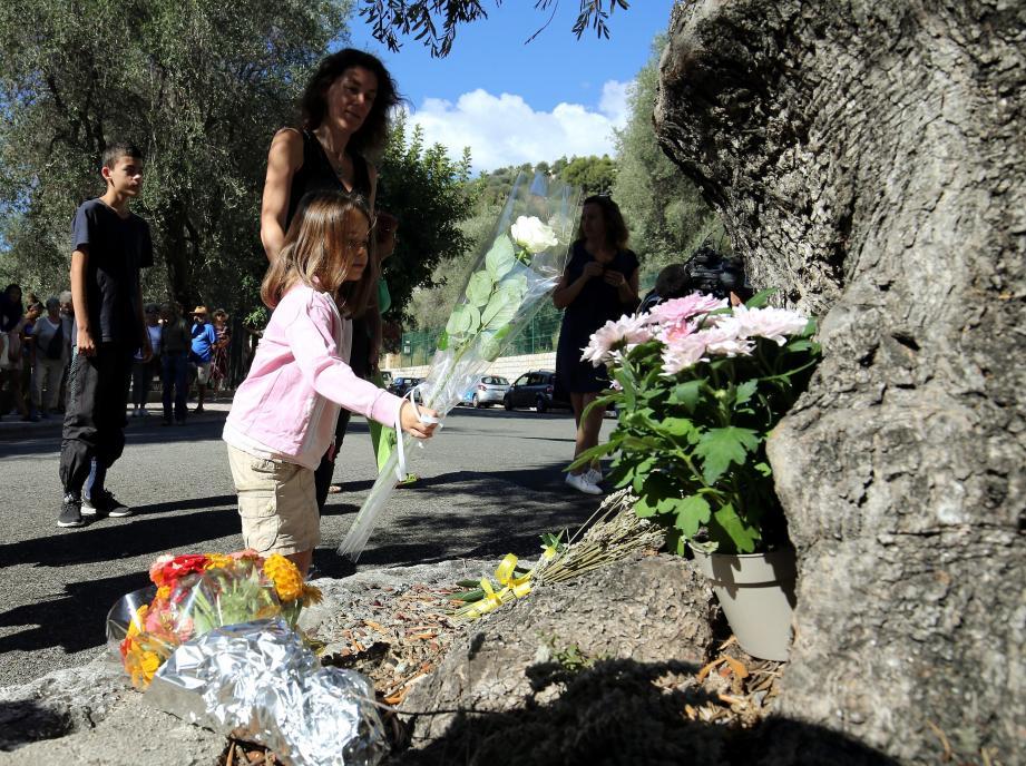 Hier à Menton, plusieurs dizaines de personnes sont venues, comme cette petite fille, déposer des fleurs en hommage au jeune migrant retrouvé mort sous le pont de l'autoroute.