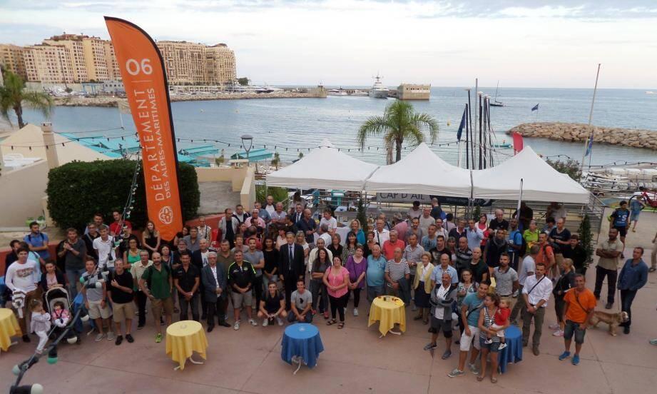 Les bénévoles du triathlon entourent Xavier Beck, le maire de Cap d'Ail, sur le parvis de la base nautique.