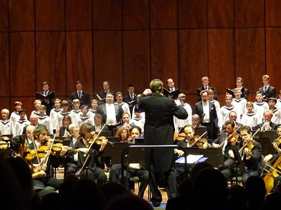 Deux rangées de garçons, dressés derrière l'orchestre, en chemisiers blancs et cols marins, ont entonné des « Gloria », « Credo » et « Agnus Dei ».