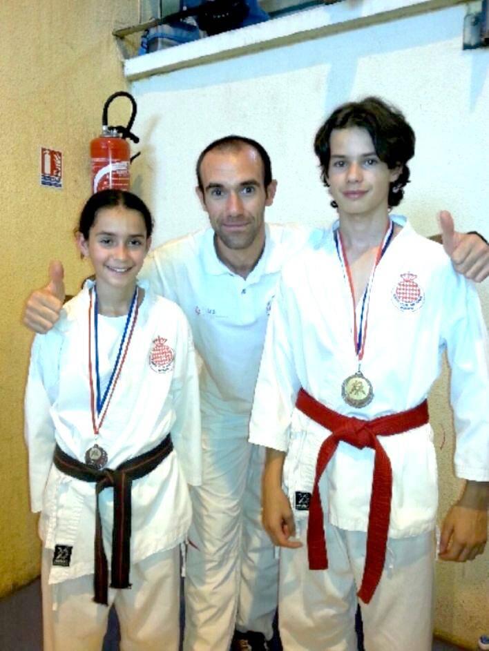 Olivia et Victor Soussan entourant leur entraîneur, Florent Carpentier.