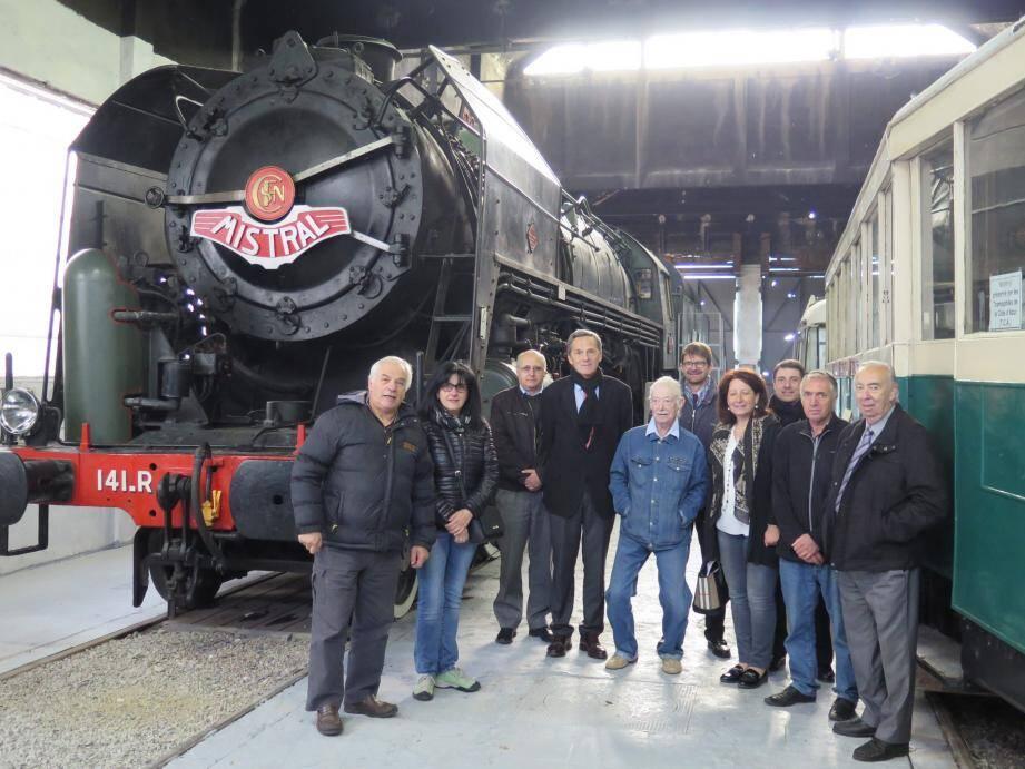 Les élus et bénévoles de l'écomusée devant les anciens trains des Merveilles.