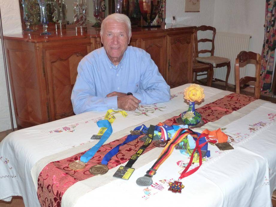 L'Antibois Bernard Boulle pose derrière les médailles de ses cinq marathons déjà bouclés.
