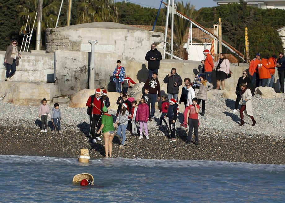 Le Père Noël plongeur et son lutin vert à sa sortie de l'eau au Cros, accueillis par les enfants du Moana