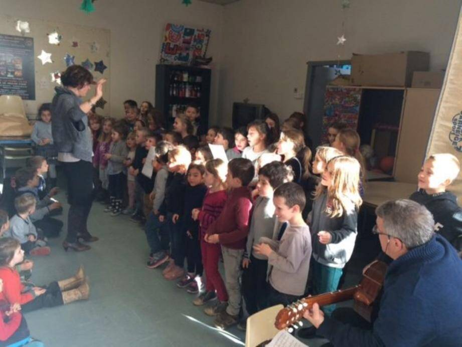 La chorale de l'école dirigée par Delphine Gaudillere, accompagnée à la guitare par Gérald Macia.