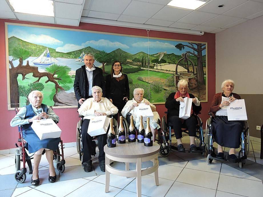 De gauche à droite : Eva Saulière (107 ans), Alice Petit (104 ans), Giovannina Ruiz (103 ans), Jeanne Canavesio (104 ans) et Victorina Mouriès (101 ans). À l'arrière-plan, Jean-Marc Illich, conseiller municipal délégué au 3° âge et Coralie Géraci, directrice des Opalines.
