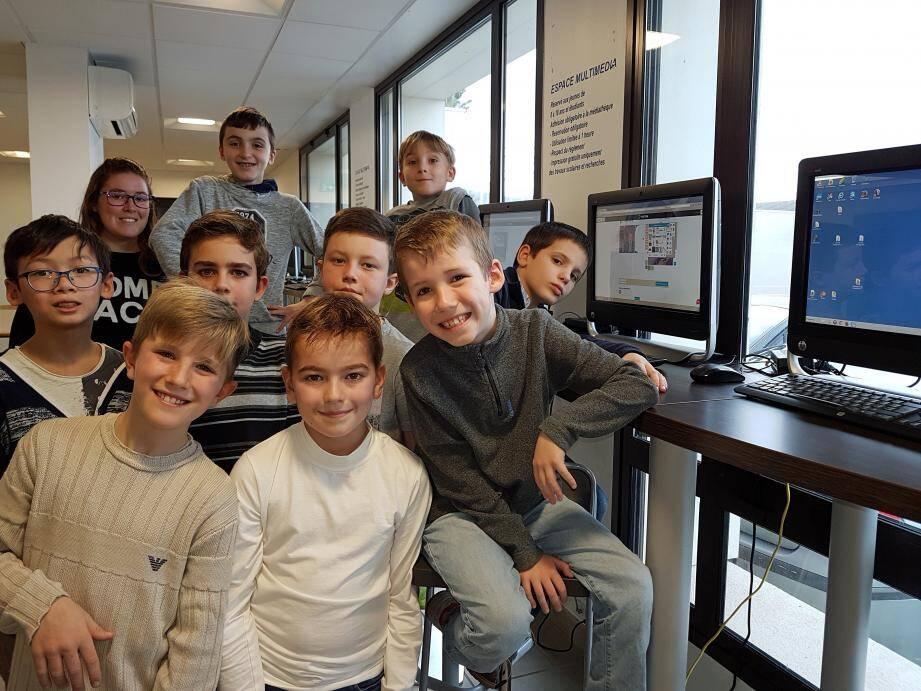 Les enfants devant les ordinateurs encadrés par Floriane.