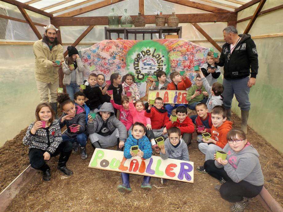 Les enfants posent, semis de salade en main, devant la fresque qu'ils ont réalisée cet été.