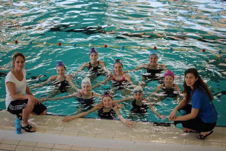 Les jeunes sportives dans l'eau avec leurs deux entraîneurs.