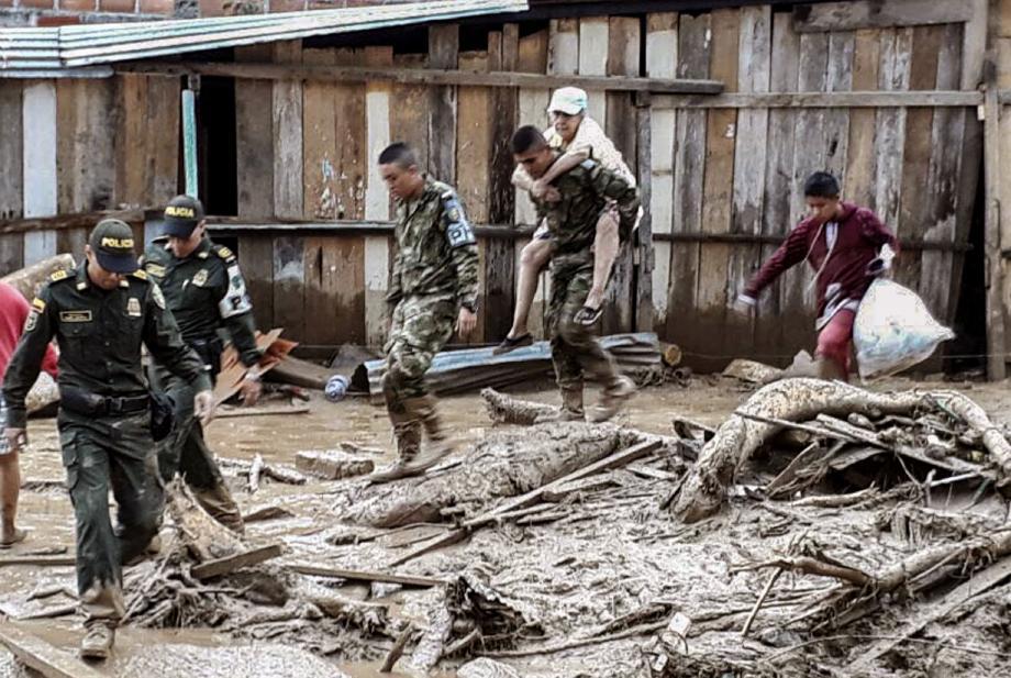A Mocoa, des soldats aident les habitants à évacuer les habitations dévastées.