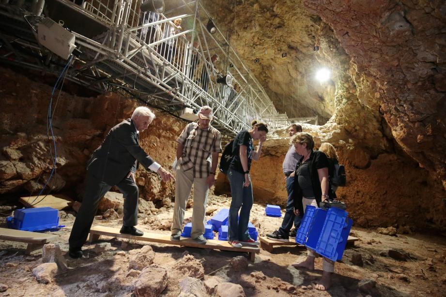 Le Professeur Henry de Lumley, directeur de l'institut de paléontologie humaine (à gauche) montrant aux scientifiques russes le sol de la grotte, au-dessus d'eux la nouvelle passerelle implantée de manière à ne pas gêner la poursuite des fouilles.