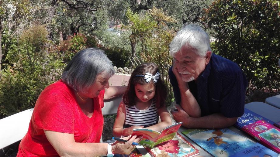 Mady et Bernard lisent une histoire à la petite Adèle dans le parc Princesse Antoinette.