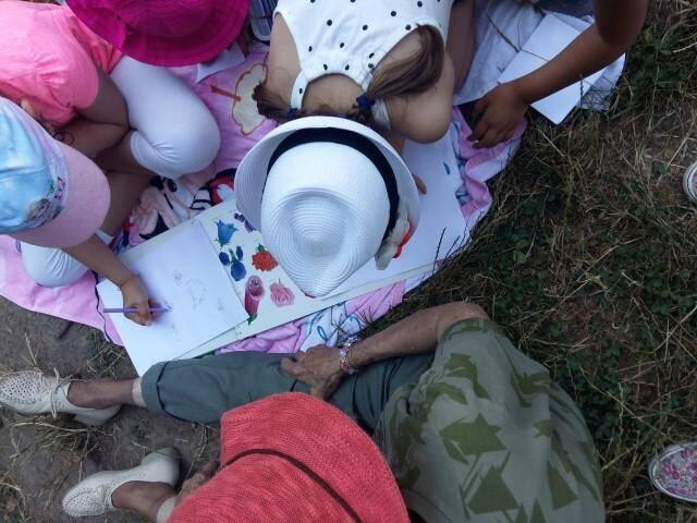 Deux enfants et un adulte : les petits groupes favorisent l'échange intergénérationnel et le partage autour d'un livre.(D. R.)
