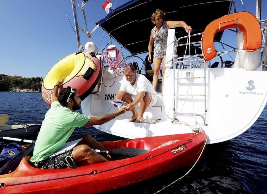 Des vacanciers originaires de La Grande Motte en train de récupérer les documents (livret, pavillon et lingette microfibre) de l'association Naturoscope, grâce aux kayaks de La Petite Flottille.