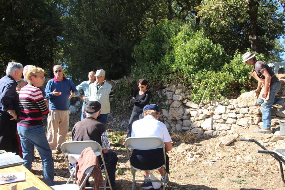 Marc Ledoux (au milieu en pull bleu) relate l'historique du château pendant que le maçon s'affaire à son mur.