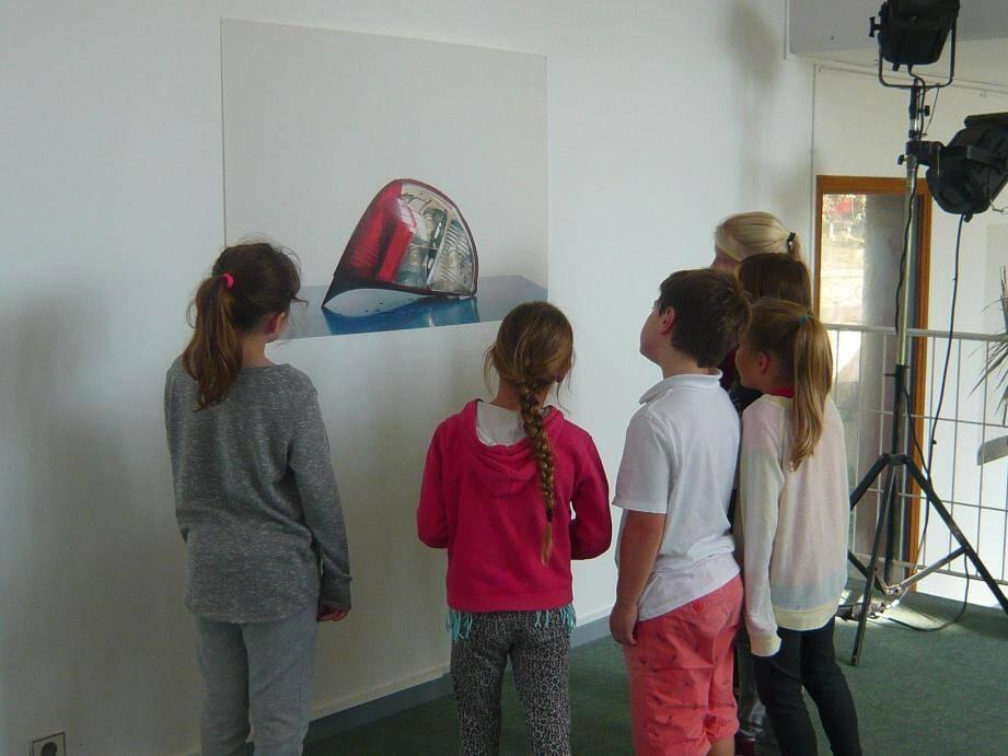 Les élèves du CM1 de l'école Marcel Pagnol étudient la photo d'un phare de voiture abîmé.