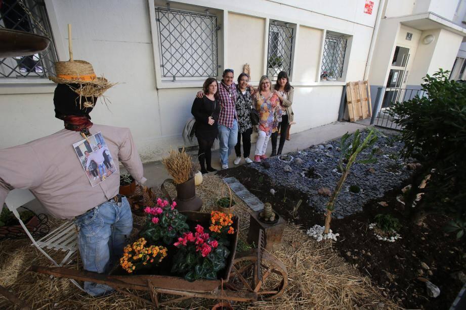 Au centre, Lydie, Jamila et Michèle, entourés de leurs « tuteurs », Violette Pessi, coordinatrice de Graines de fermier, et Maria Christodoulou, animatrice de Paje, devant l'un des jardins.
