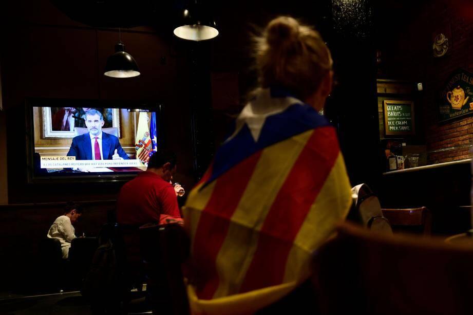 Une femme, drapée dans un drapeau catalan pro-indépendance, regarde l'allocution télévisée du roi d'Espagne.